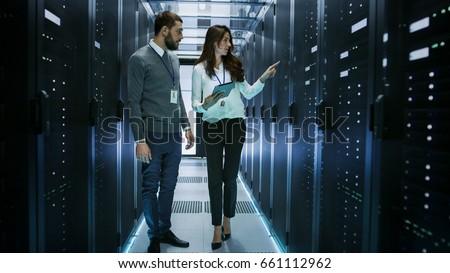 Female and Male IT Engineers Discussing Technical Details in a Working Data Center/ Server Room. #661112962