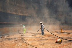 Female and male line worker surface corrosion plate preparation by sand blasting of tank internal oil