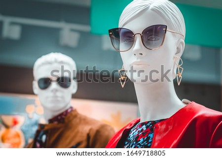 Female and male mannequins. Bright portrait of a white woman dummy in sunglasses and red jacket against background of mannequin man in store window. Family shopping. Fashion industry