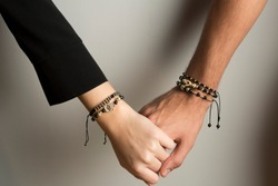 Female and male models hand with gold custom design bracelets