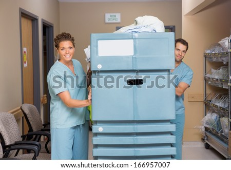 Female and male nurses pushing trolley filled with linen in hospital hallway