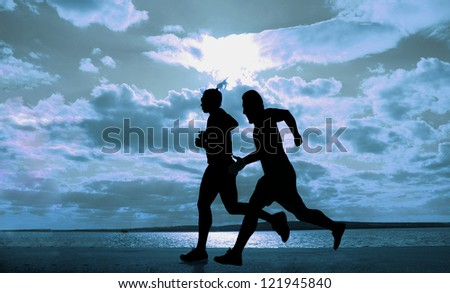 Female and male - paar -  runner full length silhouette against the blue sky and sun