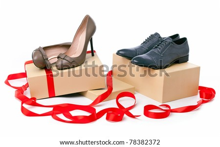 Female and male shoes on boxes with ribbon