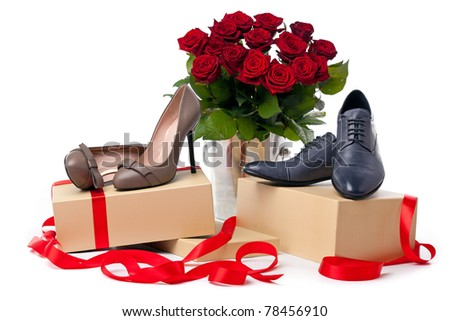 Female and male shoes on gift boxes and bunch of roses over white background