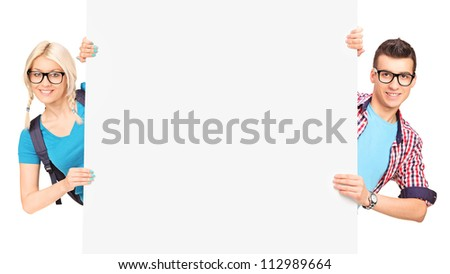 Female and male students posing behind a white panel isolated on white background