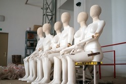 Female and male white plastic mannequins sitting on the ladder, selective focus