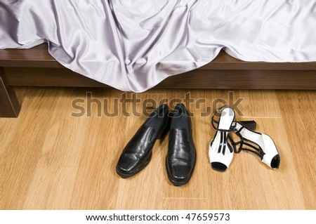 Female and man's footwear in the disorder near a bed