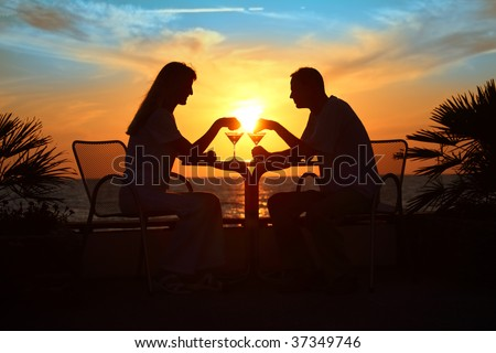 Female and man's silhouettes on sunset sit at table with two glasses outdoor