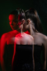 Female anxiety. Subconscious fear. Mental disorder. Double exposure blur silhouette night portrait of disturbed woman in red neon light isolated on dark green background with dust scratches.
