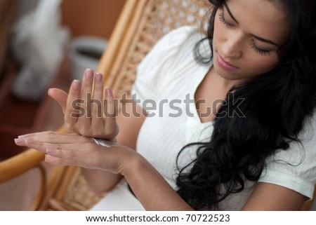 Female applying cream to her hands