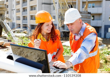 Female architect and construction worker looking at laptop together against construction
