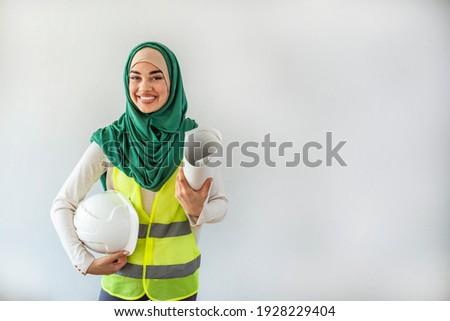 Female architect and engineer in hidjab and hardhat. Muslim architect woman. Engineer Woman hold Blue Print architects at Construction site or Building site of highrise Building.working woman concept