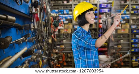 Female architect holding clipboard and gesturing against grey background against full store room