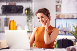 Female Architect In Office Working On Plan At Desk Taking Phone Call On Wireless Earpiece