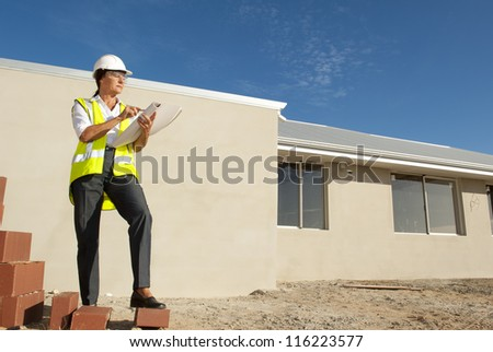 Female architect on construction site with bricks, supervising building of residential houses, isolated with wall and blue sky as background and copy space.