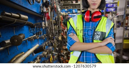 Female architect standing with arms crossed against grey background against full store room