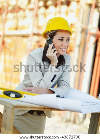 female architect talking on mobile phone in construction site