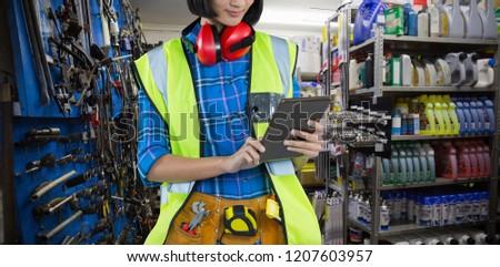 Female architect using digital tablet  against full store room