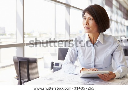 Female architect using tablet computer, looking away