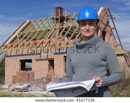 Female architect wearing blue helmet posing with building plans against unfinished brick house