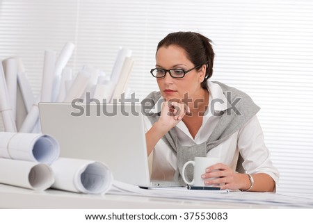 Female architect with laptop and coffee sitting at the office