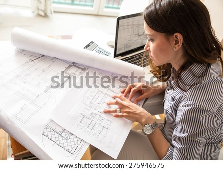 Female architect working at home.She looking blueprints.