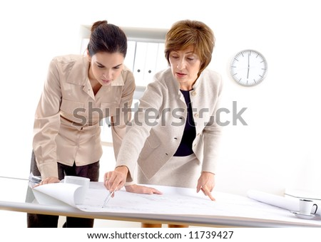 Female architects designing on blueprint at office.