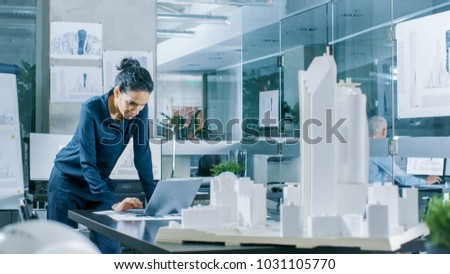 Female Architectural Designer Works on a Laptop,  Engineering New Building Model for the Urban Planning Project. Clean Minimalistic Office, Concrete Walls Covered by Blueprints and Documents. #1031105770