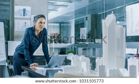 Female Architectural Designer Works on a Laptop,  Engineering New Building Model for the Urban Planning Project. Clean Minimalistic Office, Concrete Walls Covered by Blueprints and Documents. #1031105773
