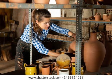 Female artisan in apron  having ceramics in stock
