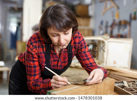 Female artisan in process of creation wooden furniture in workshop