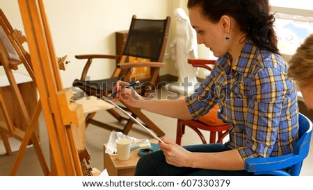 Female artist draws a pencil sketch drawing on canvas easel in art studio. Student girl learning to draw and paint. #607330379