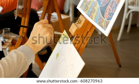 Female artist draws a pencil sketch drawing on canvas easel in art studio. Student girl learning to draw and paint. #608270963