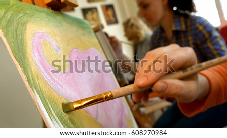 Female artist draws a pencil sketch drawing on canvas easel in art studio. Student girl learning to draw and paint. #608270984