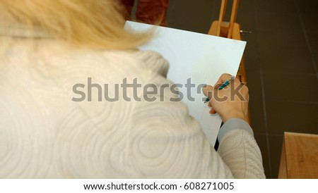 Female artist draws a pencil sketch drawing on canvas easel in art studio. Student girl learning to draw and paint. #608271005