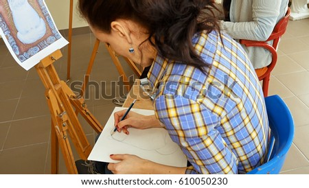 Female artist draws a pencil sketch drawing on canvas easel in art studio. Student girl learning to draw and paint. #610050230
