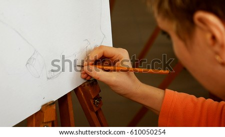 Female artist draws a pencil sketch drawing on canvas easel in art studio. Student girl learning to draw and paint. #610050254