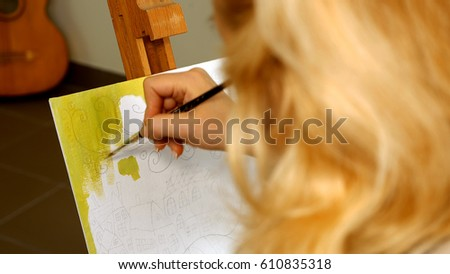 Female artist draws a pencil sketch drawing on canvas easel in art studio. Student girl learning to draw and paint. #610835318