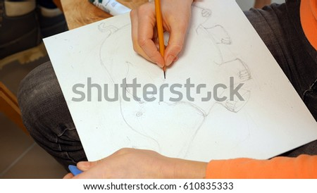 Female artist draws a pencil sketch drawing on canvas easel in art studio. Student girl learning to draw and paint. #610835333