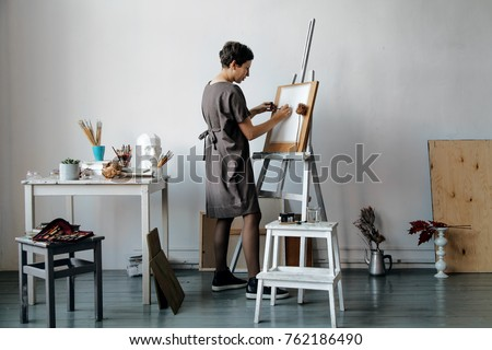 Female artist in her spacious white studio working with watercolor painting.  Natural lighting. Disclosure of creativity concept. Horizontal composition. #762186490