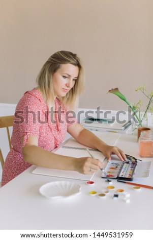 Female artist making watercolor sketches in studio. Minimal style, modern interior design. Copy space, Stylish artistic workspace.