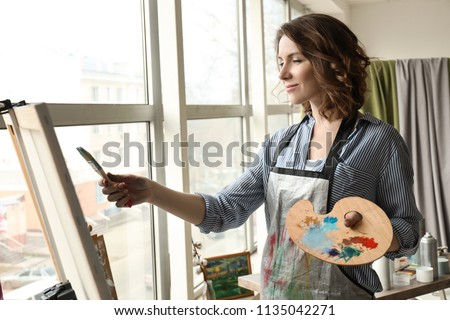 Female artist painting in workshop #1135042271