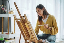 Female artist painting on canvas at home. Hobby and leisure concept.