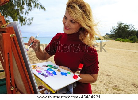 female artist painting outdoors at a beach - stock photo