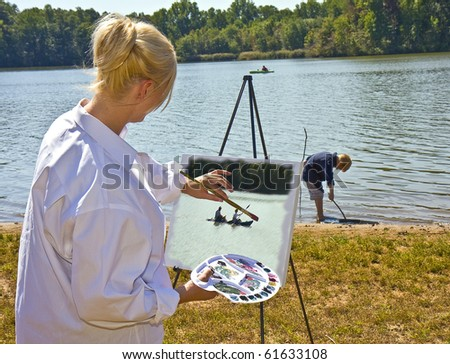 Female artist spending day with her son at park while painting scenic pictures