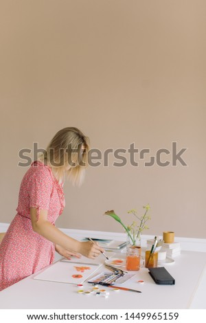 Female artist working in studio. Minimal style, modern interior design. Copy space, Stylish artistic workspace.