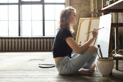 Female artist working on painting in studio in front of an empty canvas in bright daylight studio