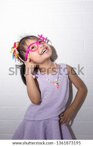 995467f6f4ae Female asian child girl posing wacky thinking pose while wearing some  accessories like crown