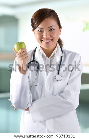 Female Asian doctor holding an apple. Healthy eating concept.