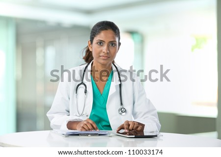 Female Asian doctor sitting at a table using a digital tablet.